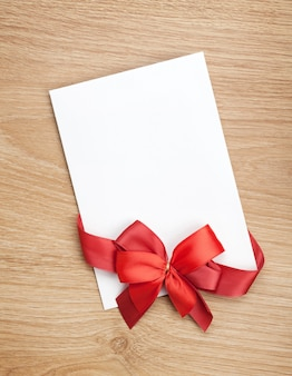Blank valentines greeting card and red ribbon on wooden background