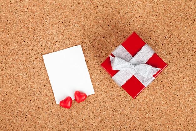 나무 배경에 빈 발렌타인 사진 프레임과 작은 빨간색 선물 상자
