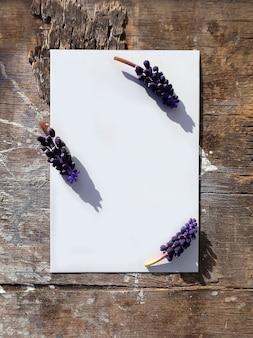 ムスカリの花と木の表面に空白の垂直紙モックアップグリーティングカード