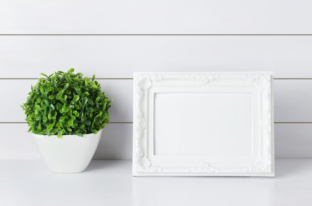 Blank vintage photo frame with green home plant
