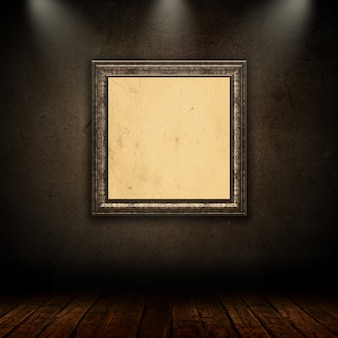 Blank vintage picture frame in grunge room with spotlights