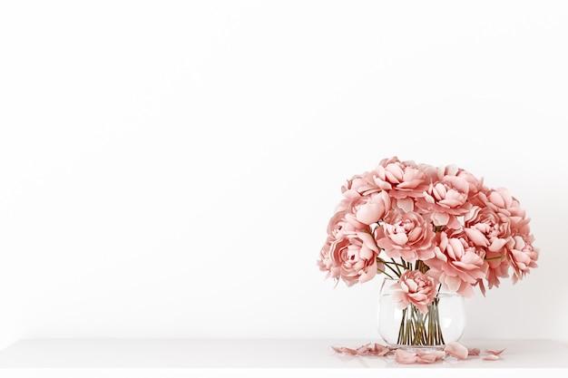 Макет пустой стены на белом фоне с розовым букетом