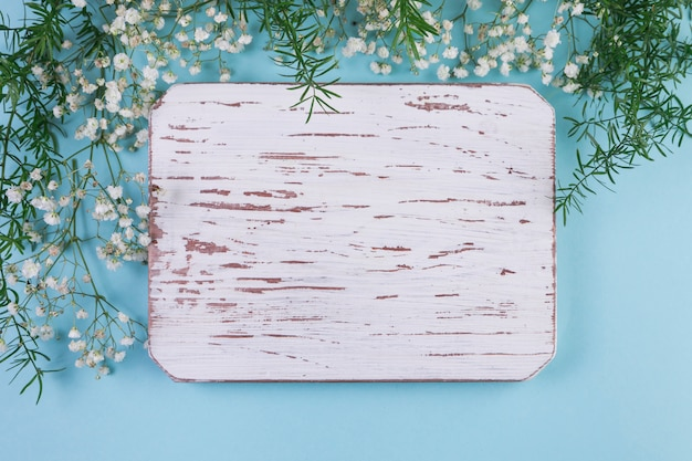 Blank weathered white wooden frame with baby's breath flowers and leaves against blue background