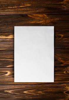 Чистый белый лист бумаги а4 на коричневый деревянный стол вертикальный