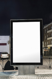 Blank white advertisement billboard on city street at night