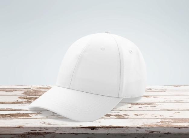Blank white baseball cap mockup on wooden desk