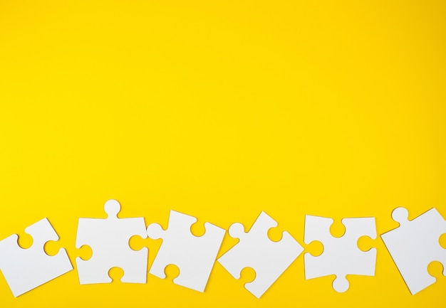 Blank white big puzzles on yellow background, flat lay