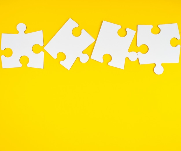 Blank white big puzzles on yellow background
