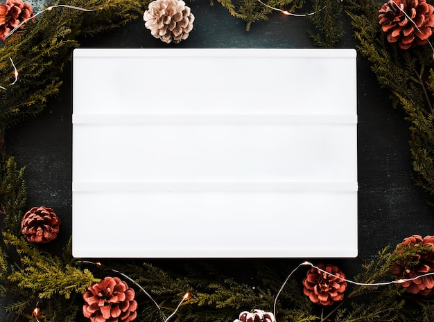 Blank white board with green branches