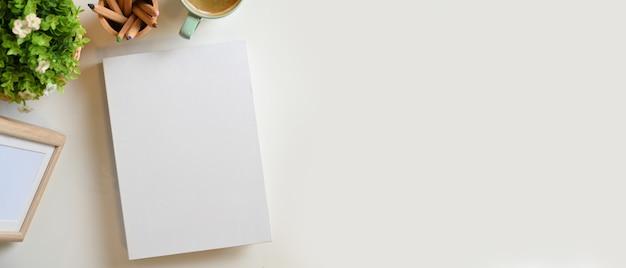 空白の白い本の表紙フレームのモックアップステーショナリーコーヒープラントのポットとモンタージュのコピースペース