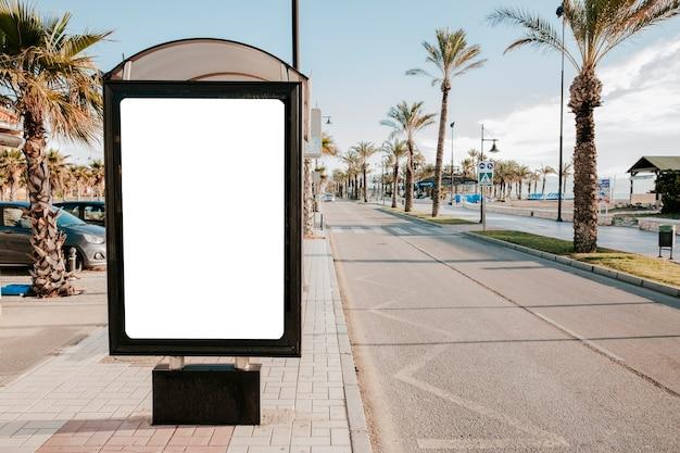햇빛에 빈 흰색 버스 정류장 상자