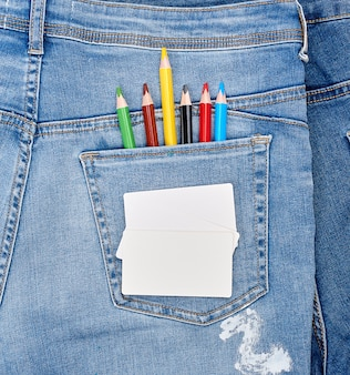 Blank white business card and colored pencils in the back pocket of blue jeans