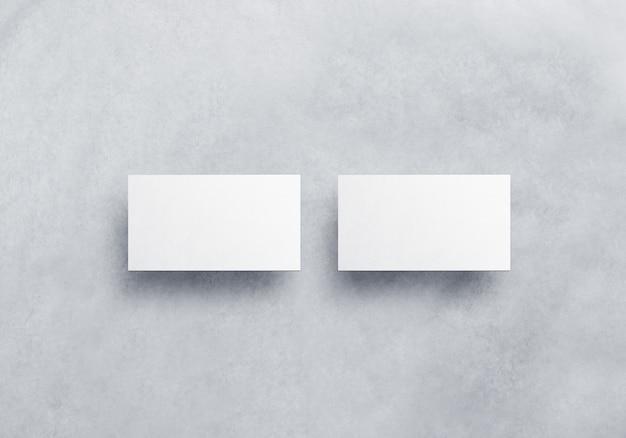 회색 질감 배경에 고립 된 빈 흰색 명함