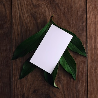 Blank white business card mockup on peony leaves wooden table background deep shadow top view