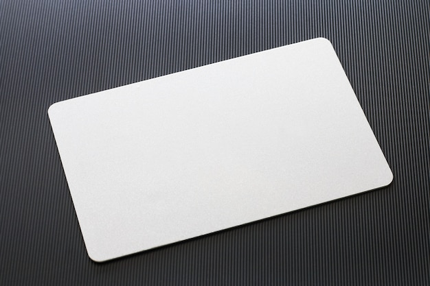 Blank white business card mockup with rounded corners on black textured background.