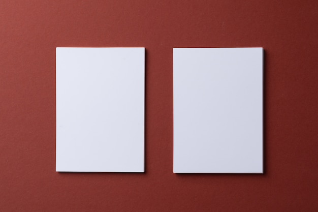 Blank white business cards on burgundy paper background