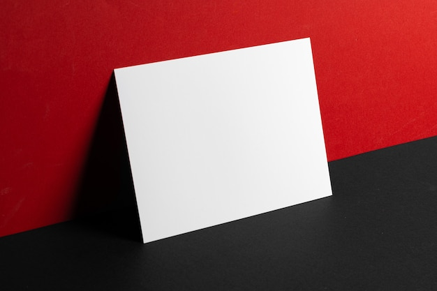 Blank white business cards on red and black paper background, copy space