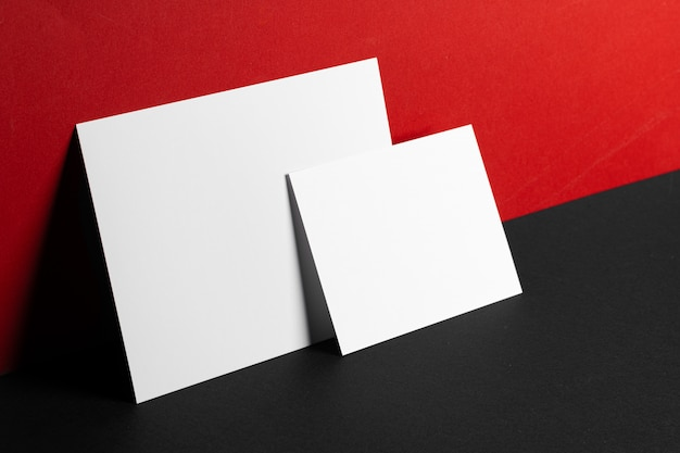 Blank white business cards on red and black table, copy space