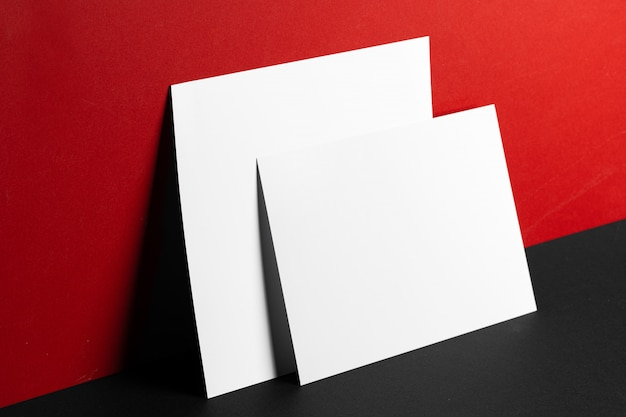 Blank white business cards on red and black table