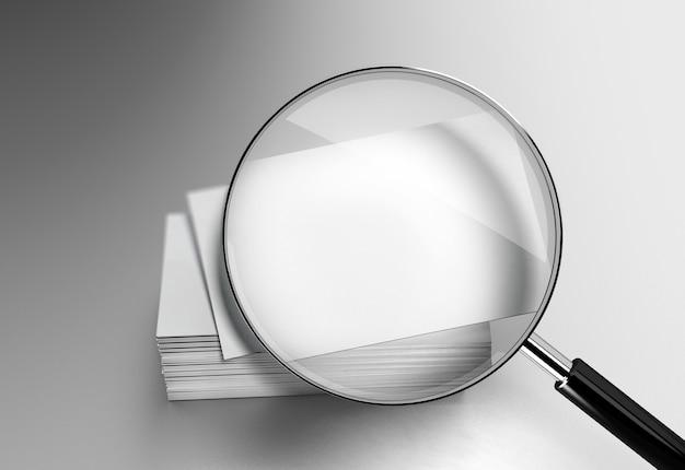 Макет стопки пустых белых визиток под увеличительным стеклом