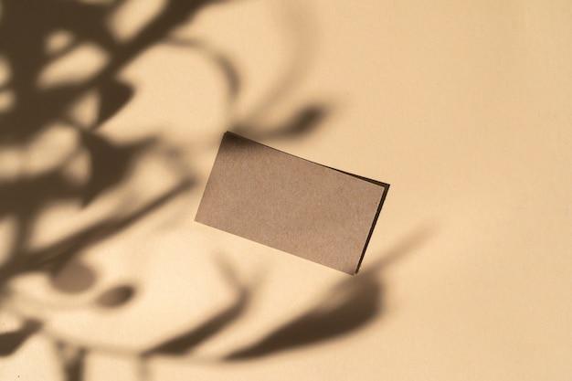 Пустая белая визитка на бежевом фоне с творческой цветочной тенью