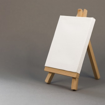 Blank white canvas on easel on gray background