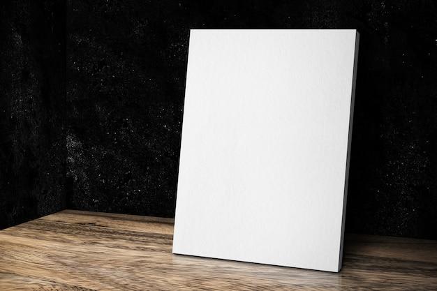 그런 지 검은 돌 벽과 나무 바닥에 기대어 빈 흰색 캔버스 프레임