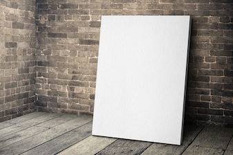 Blank white canvas frame leaning at grunge brick wall and wood floor