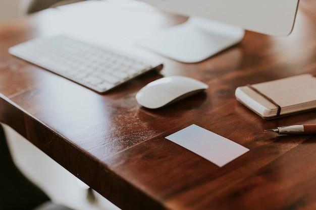 木製のテーブルの上のコンピューターのキーボードの横にある空白の白いカード