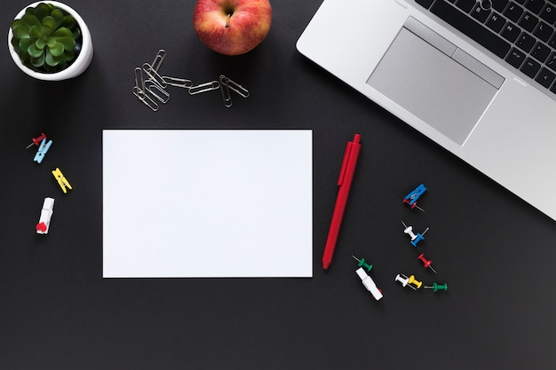 Blank white card paper with pen; apple; colorful office stationeries and laptop on black background