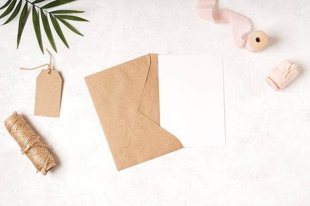 손에 공예 종이 봉투와 함께 빈 흰색 카드