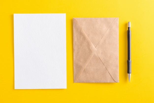 Blank white card with kraft brown paper envelope and pencil on yellow