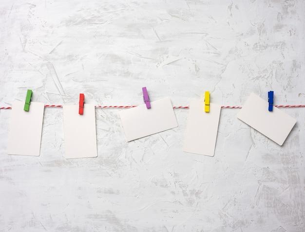 빈 흰색 골판지 직사각형 종이 조각, 흰색 시멘트 벽 배경에 매달려 종이