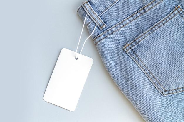 Пустая белая картонная бирка или этикетка с веревкой на фоне джинсовой одежды