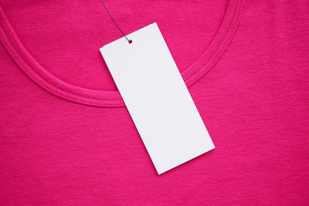 새 분홍색 셔츠에 빈 흰색 옷 태그 레이블
