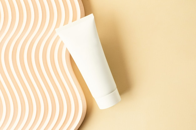 Blank white cosmetics tube on the beige background.wavy podium near it.good as cosmetic mockup,pastel banner with copy space.