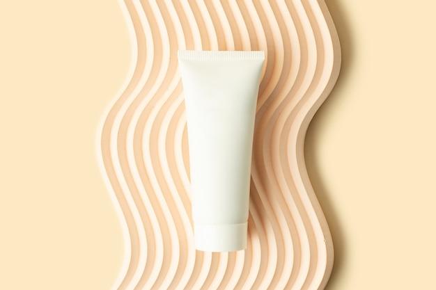 Blank white cosmetics tube on the beige backgroundwavy podium under it
