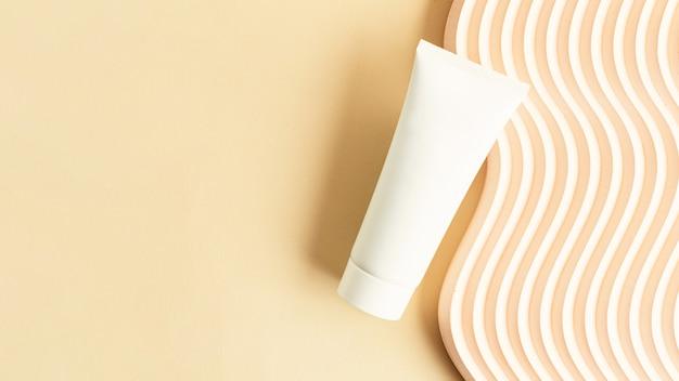 Blank white cosmetics tube on the beige backgroundwavy podium near it