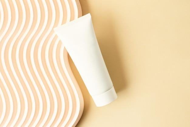 ベージュの背景に空白の白い化粧品チューブその近くの波状の表彰台化粧品のモックアップとして良い