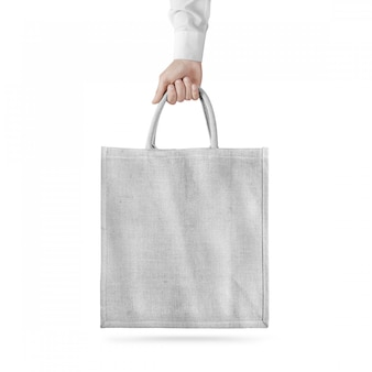 Blank white cotton eco bag design  isolated, holding hand