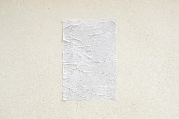 コンクリートの壁の背景に空白の白いしわくちゃと折り目付き接着剤ストリートポスターモックアップ
