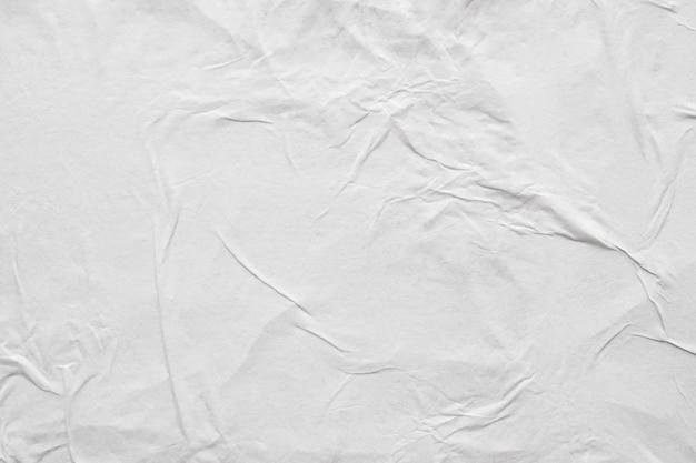 空白の白いしわくちゃにしわの紙のポスターのテクスチャ