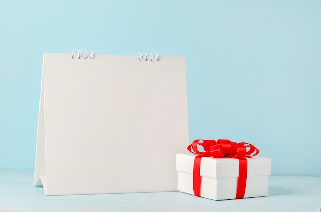 Blank white desk calendar and christmas gift box with red ribbon bow