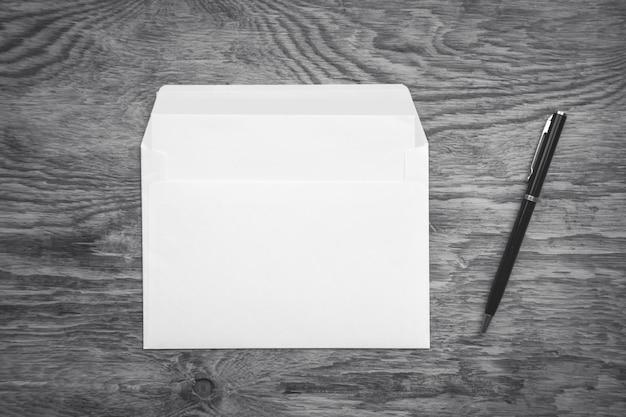 빈 흰색 봉투와 펜 나무 배경