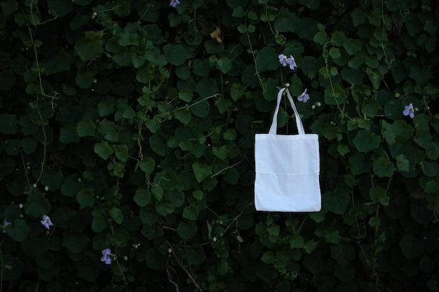 녹색 덤불 나무 단풍 배경에서 빈 흰색 패브릭 천 가방 토트