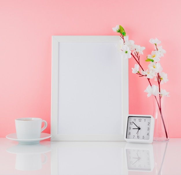 Blank white frame, flower, clock and cup of coffee or tea on whi