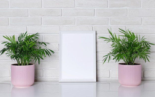 Blank white frame and house plant in pink flowerpots on a shelf near a white brick wall. modern home decor. horizontal image