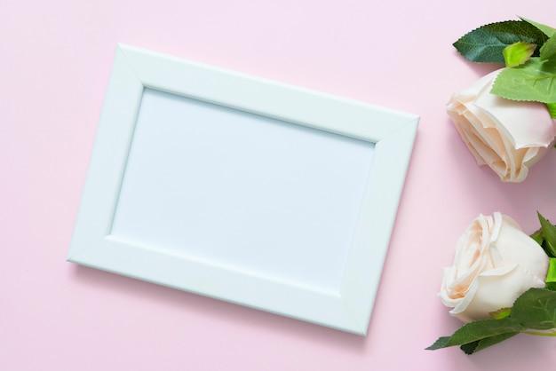 Макет пустой белой рамки с пастельными розами на розовом фоне для любовной свадьбы или дня святого валентина