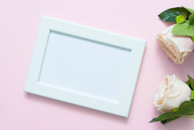 Blank white frame mockup with pastel roses on pink backgroud for love wedding or valentine day