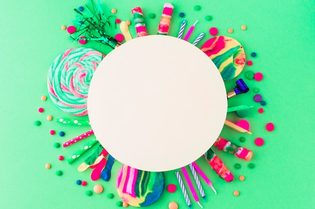 Blank white frame over party accessories and candies on green background
